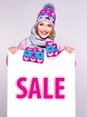 Adult smiling  woman in winter outerwear  holds the white banner with sale word on it