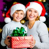 Happy mother with child hold box with gift on the christmas holiday - indoors