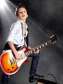 A young white boy sings and plays on the electric guitar on the stage with bright lights