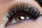 Closeup woman's eye with long black false eyelashes and  creative fashion bright makeup