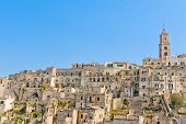 Panoramic View Of Tipical Stones And Church Of Matera Under Blue Sky