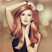 Beautiful woman with long straight red hair in a black dress touching her face. Fashion model instag