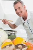 Side view portrait of a man preparing food with vegetables in the foreground at kitchen