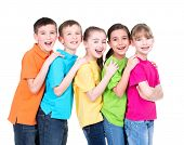 Group of happy children in colorful t-shirts stand behind each other putting hands on the shoulders