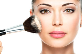 picture of foundation  - Closeup portrait of a woman  applying dry cosmetic tonal foundation  on the face using makeup brush - JPG