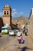 CUZCO, PERU, MAY 1, 2014: CUZCO, PERU, MAY 1, 2014: Local woman in folk costume with a Manta, which is a traditional carrying cloth, walks down a street
