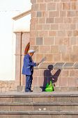 CUZCO, PERU, MAY 1, 2014: Elderly local man reads a poster in front of San Francisco church
