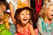 foto of sorcery  - Little laughing girl wearing dress and Halloween hat surrounded by friends kids - JPG