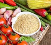 stock photo of millet  - Raw Organic millet in bowl and vegetables - JPG