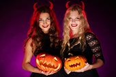 Portrait of two horned girls with jack-o-lanterns looking at camera