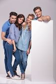 full body picture of four casual young people with a big blank billboard on grey background