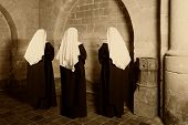 Three nuns in habit standing in a medieval abbey