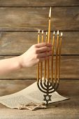 Hand burning candles on Menorah on wooden background