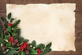 Christmas and winter background border with fir, holly, ivy, mistletoe and pine cones over old parchment paper and oak wood.