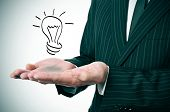 a man wearing a suit with a lightbulb drawn in his hand
