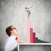 Businessman screaming at businesswoman standing on top of graph