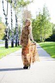 Beautiful blonde in leopard print long dress walks in autumn park