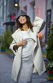 Young beautiful model in a stylish designer clothes posing on the street in the evening