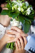 Newly wed couple holding bouquet and kissing behind it - focus on the rings