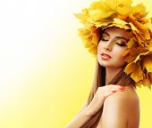 Beautiful young woman with yellow autumn wreath on yellow background