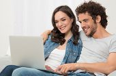 Portrait Of Happy Young Couple Sitting On Sofa Using Pc