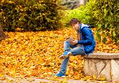 Curly Man In Blue Jacket And Scarf With Computer Tablet In Autumn