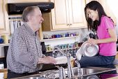 stock photo of mixing faucet  - Old man and girl washing dishes together - JPG