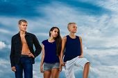 A Group Of Three Teenagers On The Beach Purposeful Looks. The Sky In The Background. Summer Vacation