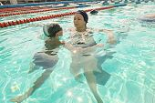 Mom and her son in swimming pool. Mother giving son a swimming lesson in pool during summer