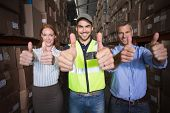 Warehouse team smiling at camera showing thumbs up in a large warehouse