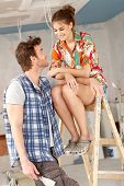 Young couple renewing home, woman sitting on top of ladder, smiling.