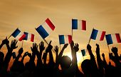stock photo of french culture  - Group of People Waving French Flags in Back Lit - JPG