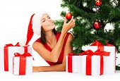 christmas, x-mas, winter, happiness concept - smiling woman in santa helper hat with many gift boxes and tree