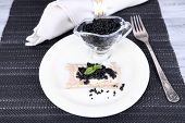 Slice of bread with butter and black caviar on plate on napkin on wooden background