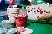 picture of poker hand  - Chips and cards for poker in hand on green table - JPG
