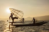Myanmar travel attraction landmark - three traditional Burmese fishermen at Inle lake, Myanmar famou