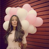 Happy young woman standing over red brick wall and holding pink and white balloons and giving air kiss. Image toned.