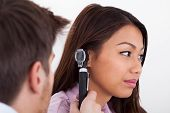 picture of otoscope  - Side view of male doctor examining patient - JPG