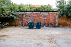 picture of dustbin  - Two green dustbins outside against red brick wall in ghetto - JPG