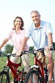 image of exercise bike  - Happy elderly seniors couple biking in park - JPG