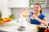 Woman pouring self-made juice into a glass, healthy food
