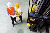 image of lift truck  - Asian fork lift truck driver discussing checklist with foreman in warehouse  - JPG