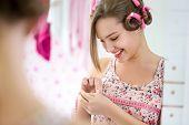Smiling girl satisfied measuring her  breast