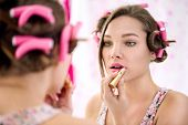 young girl in bathroom  applying lipstick and doing her make up ready
