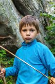 Serious Kid With A Wooden Sword On Stone