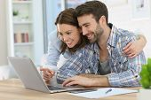 Couple at home websurfing on internet
