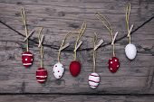 stock photo of dots  - Many Red And White Easter Eggs Hanging On A Line Which Are Dotted And Striped On Brown Wooden Vintage Or Rustic Background For Easter Greetings And Happy Easter - JPG