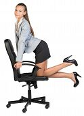 Businesswoman kneeling on office chair, looking at camera cheerfully
