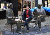 Tourist on the bench with Irish writer Oscar Wilde.