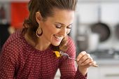 Portrait Of Happy Young Woman Eating In Kitchen